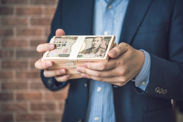 一万円札の束を持っているビジネスマン