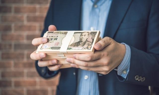 一万円札の束をスーツを着た男性が両手で持っている