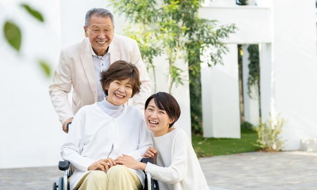 おじいちゃんが車いすのおばあちゃんの後ろで笑顔でいる様子