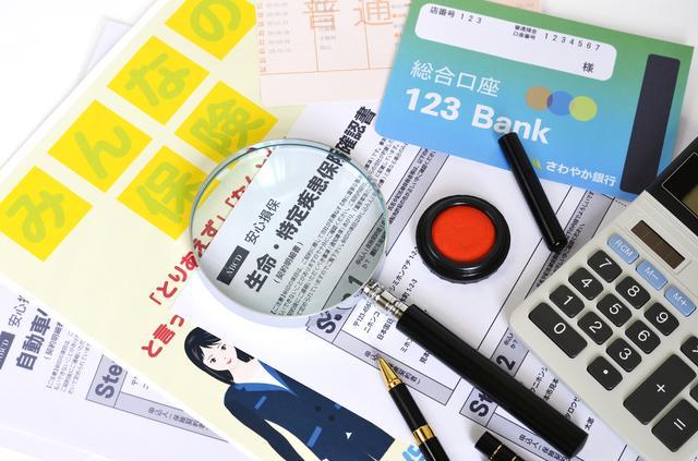 生命保険の書類や電卓、印鑑、通帳などの関連アイテム