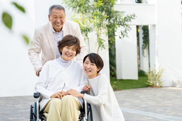 お父さんと娘が車いすの乗ったお母さんと笑顔でほほえんでいる様子