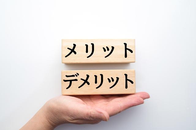 手の平の上にメリットデメリットと書かれた木の板が乗っている